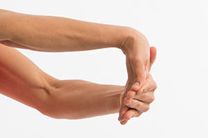 Person pulling down on fingers with one hand to extend the wrist of other hand