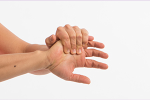 Person stretching the right hand wrist by pulling the hand toward their body with left hand