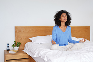 Young woman sitting cross-legged in bed meditating