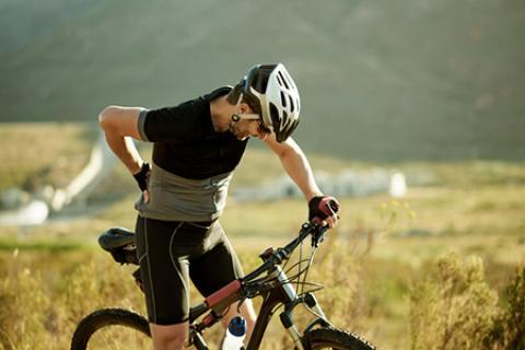 Mature man on mountain bike rubbing a sore lower back.