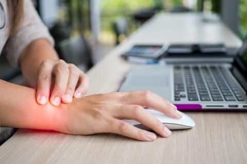 A hand on a mouse next to a computer with glowing red light on the wrist showing wrist pain