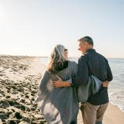 older couple walking on the beach together and smiling