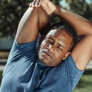 African American man stretching with one arm behind his back.