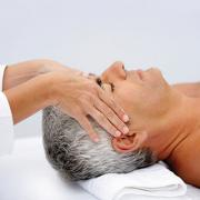 An older man receiving a head massage while lying on a massage table