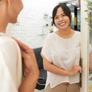 Asian woman welcoming a customer to her store.